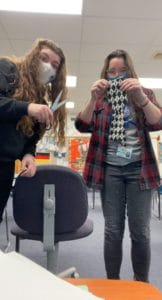 students showing scissors and cut necktie
