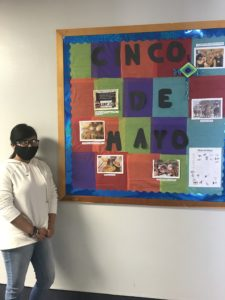 student standing next to cinco de mayo bulletin board