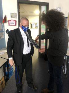 student cutting Roy Webb's necktie